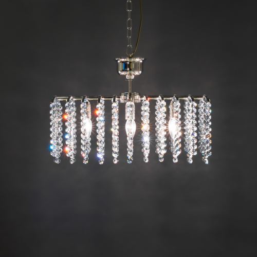 Rake 5 is an individual crystal luminaire with hanging crystal ribbons, three light points, and a nickel-plated body.